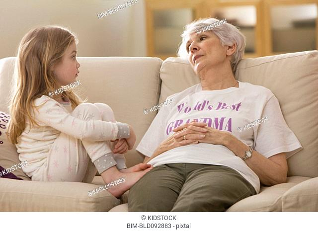Caucasian grandmother and granddaughter sitting on sofa together