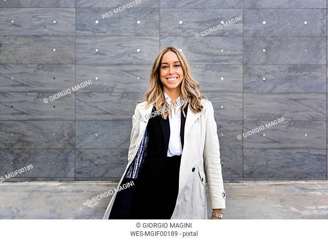 Portrait of happy businesswoman wearing trench coat