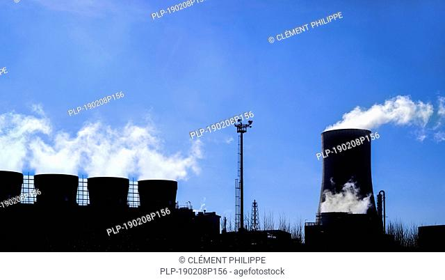 Industrial estate showing cooling tower and chimneys silhouetted against blue sky at the BASF chemical production site in the port of Antwerp, Belgium