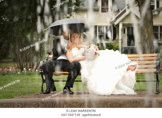 Bride and groom sitting on a park bench in the rain