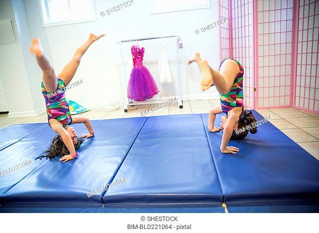 Twin sisters tumbling in gymnastics