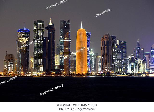 Skyline of Doha with Al Bidda Tower, Palm Tower 1 and 2, World Trade Center, Burj Qatar Tower with golden illumination, Tornado Tower, night scene