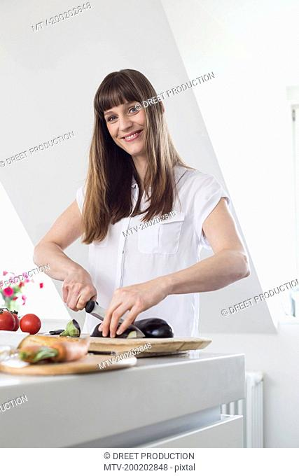 Portrait of mid adult woman cutting aubergine in kitchen, smiling