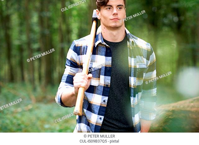 Man in forest carrying axe on shoulder