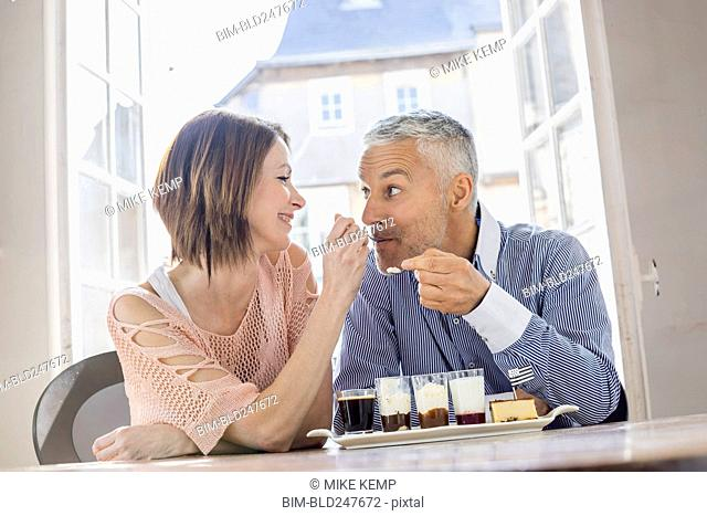 Caucasian woman feeding man dessert in restaurant