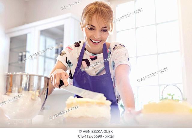 Smiling woman baking, icing layer cake in kitchen