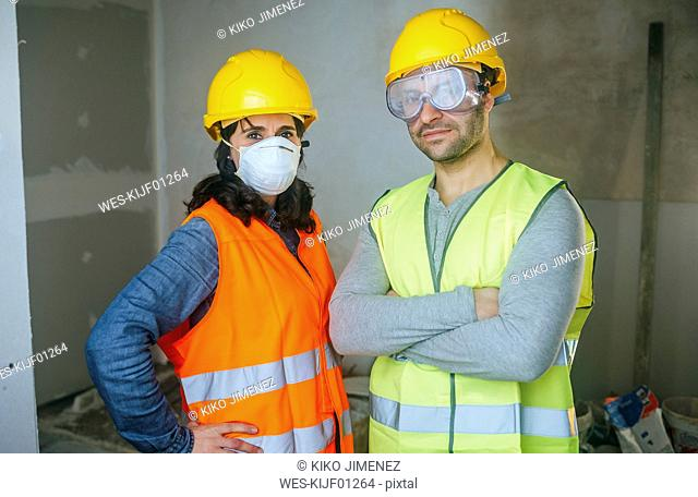 Portrait of woman with mask and man with safety glasses on a construction site