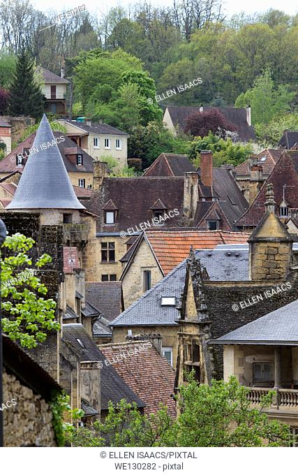 Collage of red tile rooftops emerges from medieval sandstone houses in charming Sarlat, Dordogne region of France