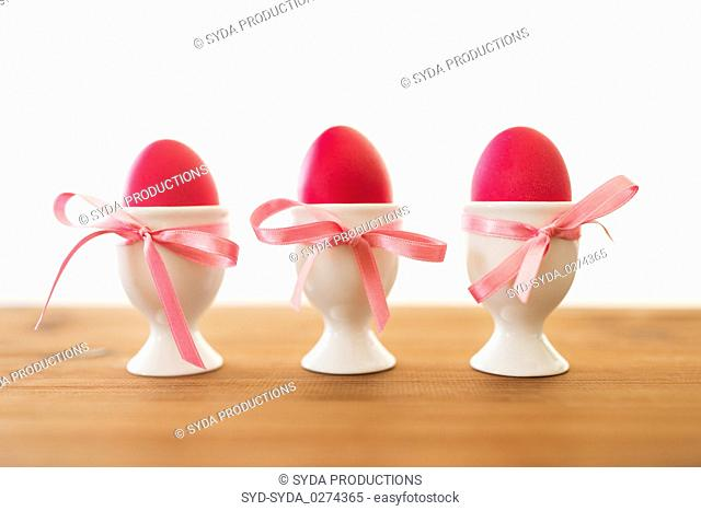 three pink colored easter eggs in holders on table
