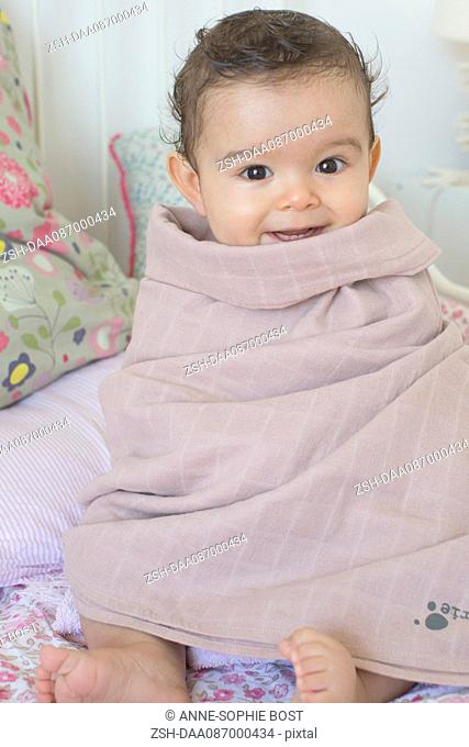 Baby wrapped in a towel after a bath, portrait