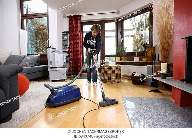 House work, woman hoovering in a flat