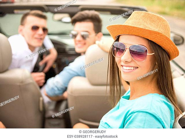 Happy friends sitting in the cabriolet, looking back and smiling at camera