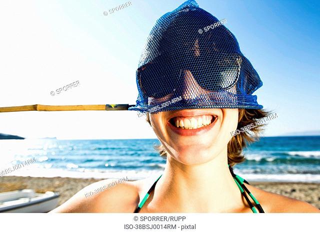 Woman holding fishing net on head