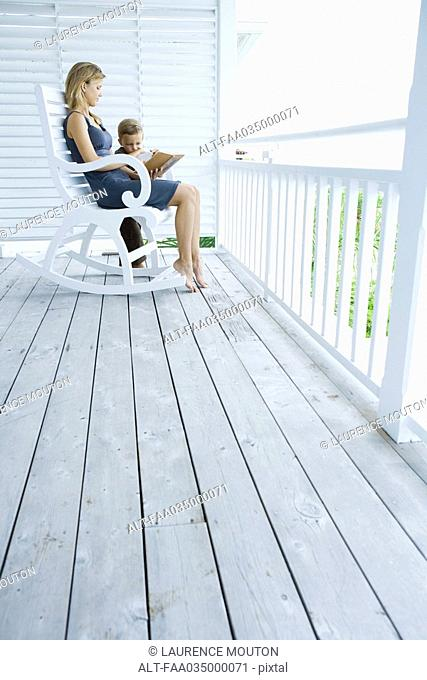 Woman sitting in rocking chair on porch, reading story to little boy standing at her side
