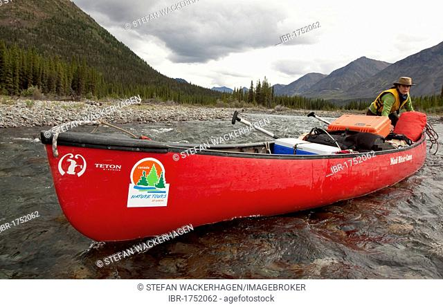 Young woman lining, wading, pushing, pulling a canoe in shallow water, Wind River, Mackenzie Mountains behind, Yukon Territory, Canada
