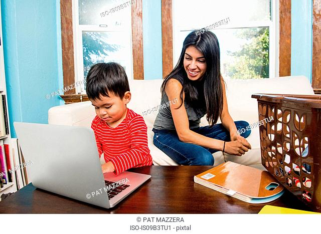 Male toddler with mother typing on laptop at home