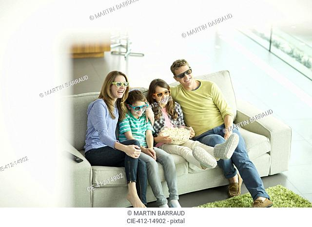 Family watching 3D television in living room