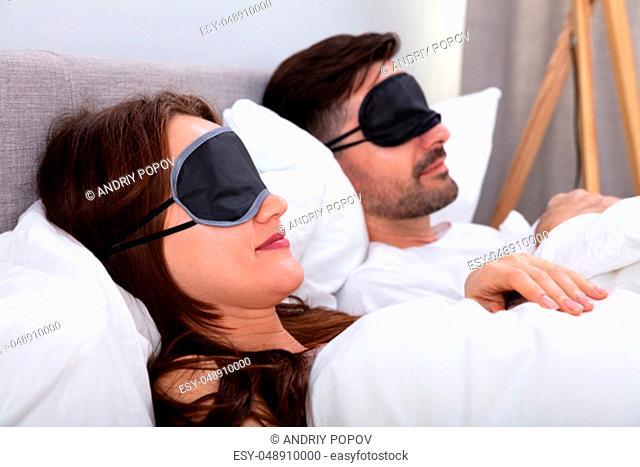 Young Couple Sleeping On Bed Using Eye Mask In Bedroom