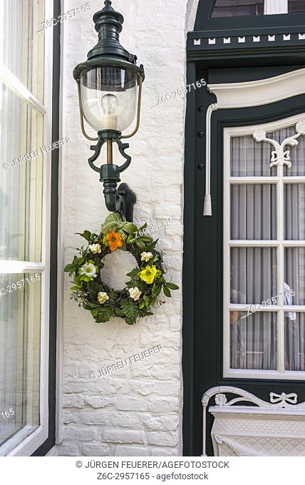 artful house door of wood with floral decoration, coastal town Husum at the North Sea, Germany