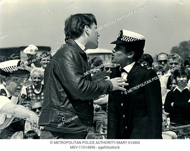 Woman police officer (Betty Reid) taking part in a self-defence demonstration exercise, dealing with an aggressive man in a leather jacket