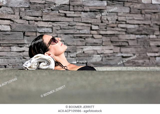 A mature woman relaxes in a hot tub while visiting the Kingfisher Resort and spa. Courtenay, Vancouver Island, british Columbia, Canada