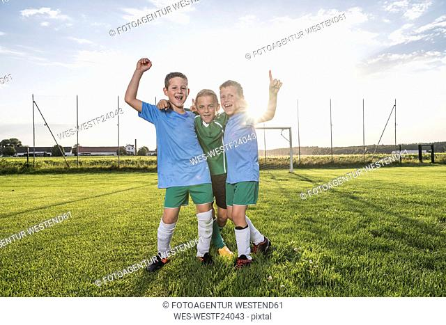 Young football players cheering on football ground