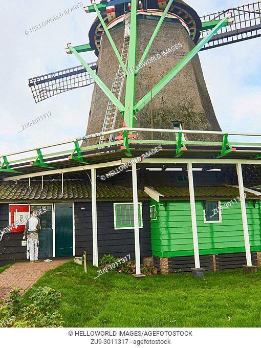 Two men painting and repairing windmill, Zaanse Schans a village near Zaandijk in the municipality of Zaanstad, North Holland, Netherlands