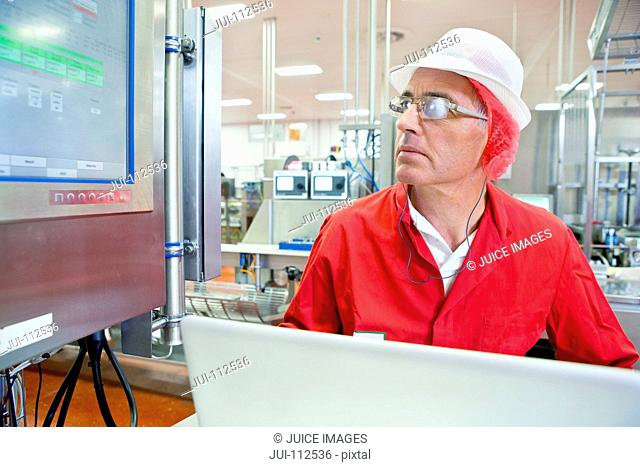 Worker watching control panel computer monitor at production line in food processing plant