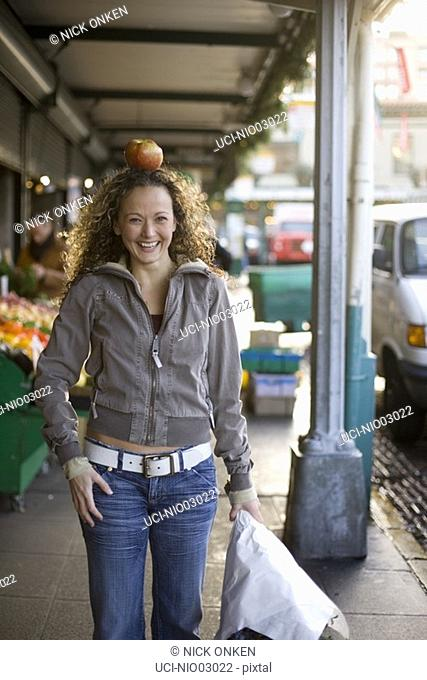 Young woman balancing an apple on her head, Pike Place Market, Seattle, Washington