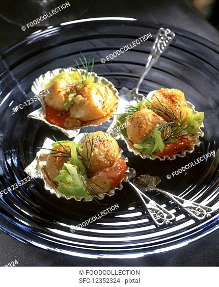 Scallops served with vegetables in silver mussel shells
