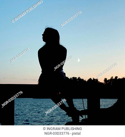 Silhouette of a woman sitting on a railing, Lake of the Woods, Ontario, Canada
