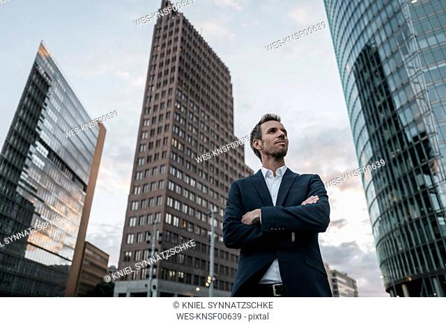 Germany, Berlin, businessman with arms crossed standing at Potsdamer Platz