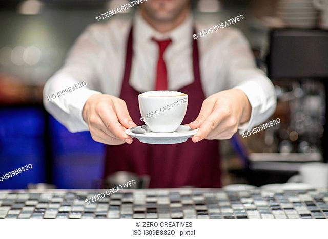 Waiter in restaurant, holding freshly made coffee, mid section