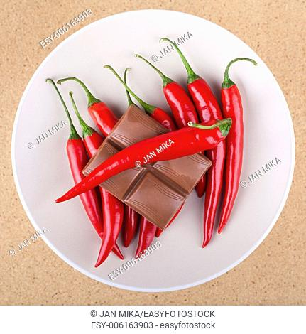 Fresh red hot chili peppers with chocolate on plate, over light wooden background