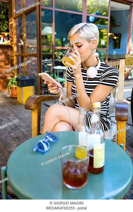 Young woman at pavement cafe enjoying soft drink while looking at smartphone
