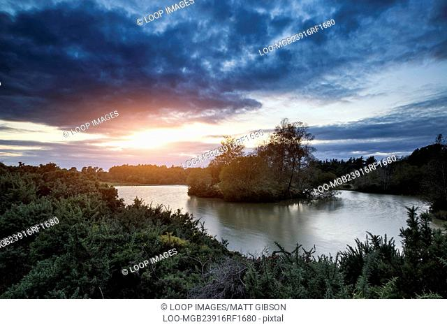 Beautiful Autumn sunset over lake landscape in forest