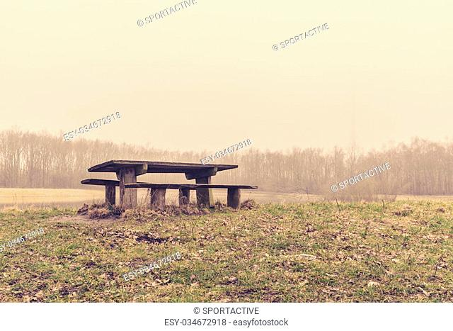 Bench in a park in the mist at autumn