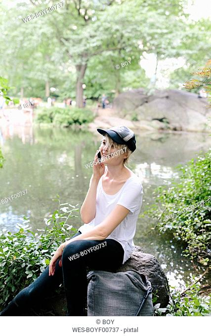 Young woman sitting at lakeside in park talking on cell phone