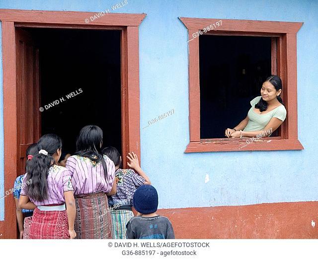Women in window watching activity in Santiago Atitlan, Solola, Guatemala