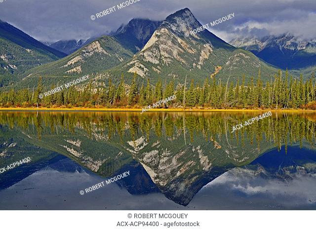 A horizontal landscape image of the rocky mountains of Jasper National Park reflecting in the calm water of Jasper Lake