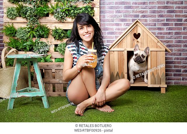 Woman and french bulldog in front of dog house and vertical garden