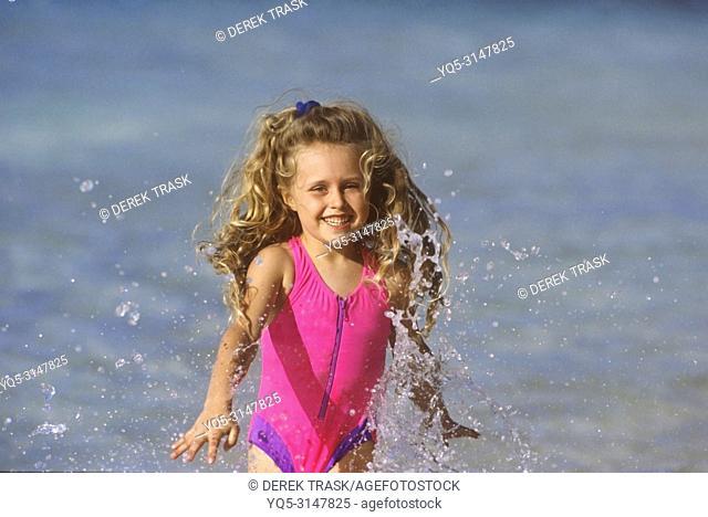 girl splashing in waves on beach