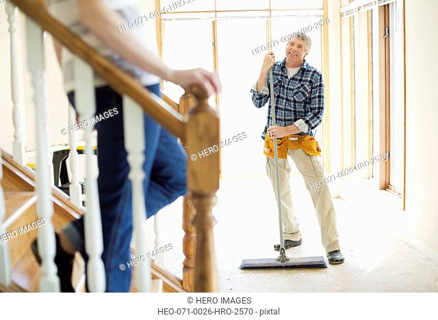 middle aged man sweeping up during renovation