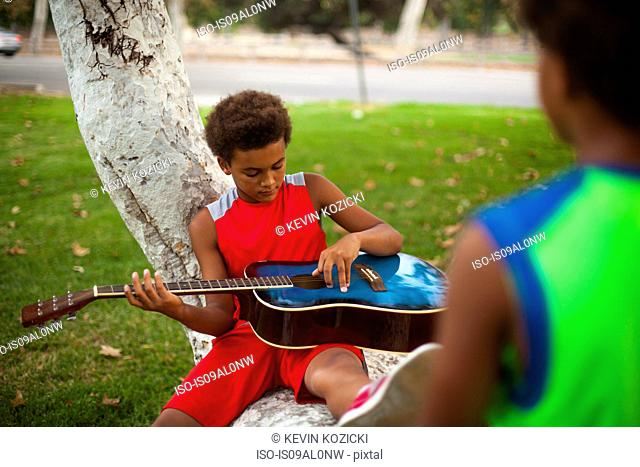 Two brothers sitting on park tree branch playing acoustic guitar