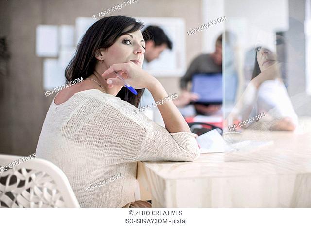 Female designer daydreaming at desk in design studio