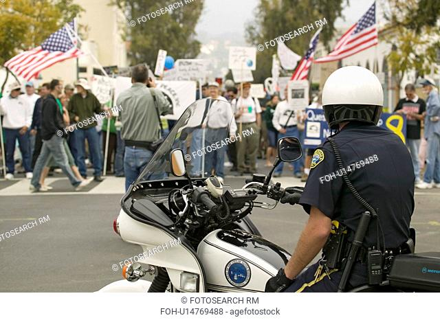 A motorcycle policeman looks at protesters against George W. Bush and the Iraq War at an anti-Iraq War protest march in Santa Barbara, California on March 17