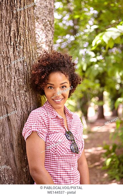 Smiling young girl looking happily at the camera in the dappled afternoon sunshine while leaning against a tree wearing casual clothing