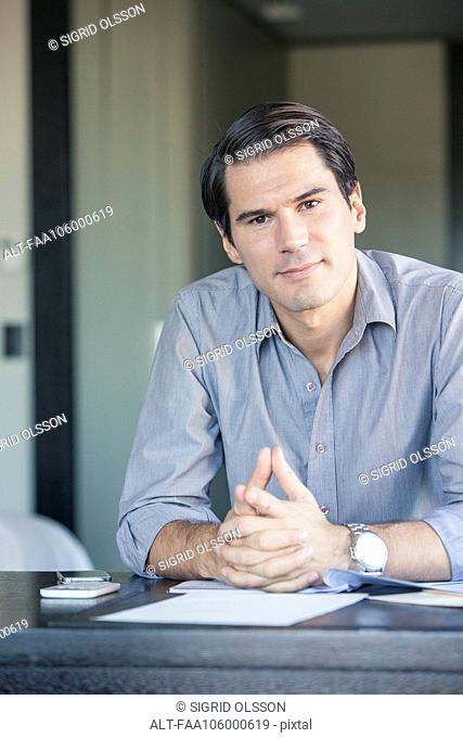 Businessman sitting at desk with clasped hands, portrait