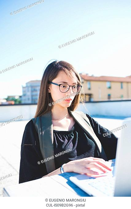 Young woman on city roof terrace typing on laptop