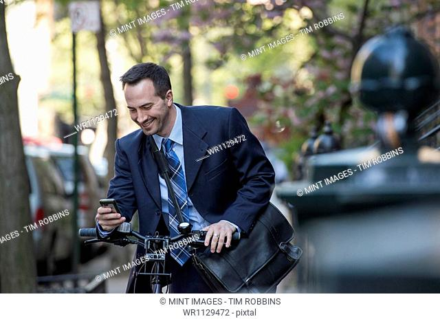 A man in a business suit, outdoors in a park. Sitting on a bicycle, with a cycle helmet in his hands